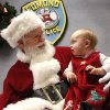 Santa stopped by the Edmond police station Saturday, Dec. 22, 2012, to visit with children, hear their Christmas lists and pose for keepsake photos that were provided for the children by Edmond police department. Checking out Santa is Clara Dunn, 10months old. Playing Santa is Boyd Mize, a retired detective with the Edmond police department. This is the eighth year Mize has donned the Santa suit for the police department\'s day with Santa. But Mize said this is the first year he didn\'t have to wear a fake beard; all the hair on Santa\'s face is natural this year. Photo by Jim Beckel, The Oklahoman