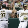 Photo - Oakland Athletics' Josh Reddick, right, is greeted by teammate Brandon Moss, left, after scoring in the fourth inning of their interleague baseball game against the New York Mets Wednesday, Aug. 20, 2014, in Oakland, Calif. Both Reddick and Moss scored after the Athletics' Andy Parrino reached on a fielding error by Mets second baseman Daniel Murphy. (AP Photo/Eric Risberg)