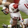 Roy Finch (22) stretches for extra yards with Londell Taylor (13) holding onto his ankles during the University of Oklahoma (OU) football team\'s annual Red and White Game at Gaylord Family/Oklahoma Memorial Stadium on Saturday, April 14, 2012, in Norman, Okla. Photo by Steve Sisney, The Oklahoman