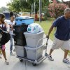 Photo -  Incoming freshman T'Aira Frazier, left, from Lawton, gets help from her cousin L'Eiric Houston, 11, and her dad, Christopher Green, during move-in day at the University of Central Oklahoma in Edmond. PHOTO BY DOUG HOKE, THE OKLAHOMAN   DOUG HOKE -  THE OKLAHOMAN