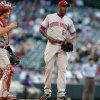Photo - Cincinnati Reds catcher Devin Mesoraco, left, talks with relief pitcher Aroldis Chapman with the bases loaded against in the ninth inning of a baseball game against the  the Colorado Rockies in Denver on Sunday, Aug. 17, 2014. The Rockies won 10-9. (AP Photo/David Zalubowski)