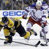 Boston Bruins left wing Brad Marchand (63) gets to the puck ahead of New York Rangers right wing Derek Dorsett (15) during the second period in Game 2 of the NHL Eastern Conference semifinal hockey playoff series in Boston, Sunday, May 19, 2013. (AP Photo/Elise Amendola)