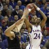 Kansas\' Travis Releford (24) shoots over Texas Ioannis Papapetrou during the first half of an NCAA college basketball game on Saturday, Feb. 16, 2013, in Lawrence, Kan. (AP Photo/Ed Zurga)