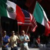 From left, Eric Nava, Luis Moreno, and Gregory Justus carry the Mexican and American flags as they join immigrants and activists during a march in Chicago calling for comprehensive immigration reform, Wednesday, May 1, 2013. (AP Photo/Charles Rex Arbogast)