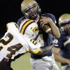 Heritage Hall\'s Connor McGinnis (4) is taken down by Clinton\'s Marquez Simpkins (24) during a high school football game between Heritage Hall and Clinton in Oklahoma City, Friday, Sept. 7, 2012. Photo by Garett Fisbeck, The Oklahoman