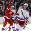 Photo - Detroit Red Wings left wing Johan Franzen, left, celebrates a second period goal by teammate Daniel Alfredsson as New York Rangers center Dominic Moore, right, skates away during an NHL hockey game Saturday, Oct. 26, 2013, in Detroit. (AP Photo/Duane Burleson)