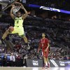 Photo - Baylor's Rico Gathers (2) scores as Nebraska's Shavon Shields (31) looks on during the first half of a second-round game in the NCAA college basketball tournament Friday, March 21, 2014, in San Antonio. (AP Photo/Eric Gay)