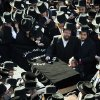 FILE - In this file photo of March 3, 2013, mourners surround a casket outside the Congregation Yetev Lev D\'Satmar synagogue at the funeral for two expectant parents who were killed in a car accident early Sunday, in the Brooklyn borough of New York. The baby of Nachman and Raizy Glauber, a boy, was delivered prematurely cesarean section and survived until the next morning but died around 5:30 a.m. on Monday, March 4, 2013. Police were searching for the driver of a BMW and a passenger who fled on foot after slamming into the livery cab that transporting the 21-year-old couple to a hospital. (AP Photo/John Minchillo, File)
