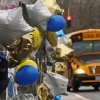 A school bus rolls towards a memorial for victims of the school shooting in Newtown, Conn., Tuesday, Dec. 18, 2012. Classes resume Tuesday for Newtown schools except those at Sandy Hook. Buses ferrying students to schools were festooned with large green and white ribbons on the front grills, the colors of Sandy Hook. At Newtown High School, students in sweatshirts and jackets, many wearing headphones, betrayed mixed emotions. Adam Lanza walked into Sandy Hook Elementary School in Newtown, Friday and opened fire, killing 26 people, including 20 children, before killing himself. (AP Photo/Charles Krupa) ORG XMIT: CTCK102
