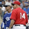 Photo - Los Angeles Dodgers manager Don Mattingly and Los Angeles Angels manager Mike Scioscia wait on the field as umpires check an instant replay during the first inning of an exhibition spring training baseball game Thursday, March 6, 2014, in Tempe, Ariz. (AP Photo/Morry Gash)