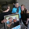 Photo - Victoria Smith Weiland, left, from Eugene, Ore., holds a picture of her and her partner Peggy McComb, as McComb hugs Aubrey Chonbold, right, on the steps of the Wayne L. Morse U.S. Courthouse Wednesday, May 14, 2014, in Eugene, Ore. A federal judge will hear arguments Wednesday about whether a national group can defend Oregon's ban on same-sex marriage because the state's attorney general has refused to do so. (AP Photo/The Register-Guard, Chris Pietsch)