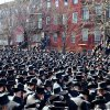 In this March 3, 2013, photo provided by VosIzNeias.com, Orthodox Jewish mourners gather outside the Congregation Yetev Lev D\'Satmar synagogue in Brooklyn\'s Williamsburg neighborhood for the funeral of two expectant parents who were killed in a car accident early Sunday, in New York. The baby of Nachman and Raizy Glauber, a boy, was delivered prematurely by cesarean section and survived until the next morning, but died around 5:30 a.m. on Monday,March 4. Police were searching for the driver of a BMW and a passenger who fled on foot after slamming into the livery cab that was transporting the 21-year-old couple to a hospital. (AP Photo/VosIzNeias.com, Eli Wohl)