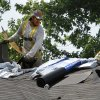 A roofer applies material to a roof of a house near Telephone Road on Tuesday in Moore. Photo by Steve Sisney, The Oklahoman STEVE SISNEY