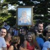 A supporter of Britain\'s Prince William and his wife Kate, Duchess of Cambridge, holds up a frame painting of their son Prince George featuring a koala and kangaroo before William\'s and Kate\'s visit to a surf lifesaving demonstration at Sydney\'s Manly Beach, Friday, April 18, 2014. The Royal couple are undertaking a 19-day official visit to New Zealand and Australia with their son, George. (AP Photo/Jason Reed, Pool)