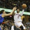 Photo - Cleveland Cavaliers' Kyrie Irving (2) shoots against New York Knicks' Andrea Bargnani, from Italy, in the second quarter of an NBA basketball game Tuesday, Dec. 10, 2013, in Cleveland. (AP Photo/Mark Duncan)