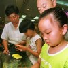 FILE - In this July 13, 1997 file photo, nine-year-old Zhu Ying tries out a Tamagotchi electronic pet at a Beijing department store. Bandai Co. and Sync Beatz Entertainment are hoping to revive the electronic pet craze of the 1990s with a new mobile app launching Thursday, Feb. 14, 2013, for Android devices. The app duplicates the egg-shaped plastic toy that became a must-own sensation after it was first released in 1996 in Japan. (AP Photo/Greg Baker, File)