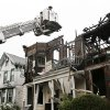 Photo - A firefighter uses a ladder to examine the damaged roof of 203 and 205 Chestnut Avenue in the Staten Island borough of New York, Thursday, June 5, 2014 after fire tore through three adjacent townhouses early Thursday, injuring 34 people. Witnesses and authorities said two young children were tossed out of a window into the arms of neighbors below. (AP Photo/Kathy Willens)