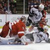 Photo - Colorado Avalanche right wing Chuck Kobasew (12) slides into Detroit Red Wings goalie Jimmy Howard (35) during the first period of an NHL hockey game in Detroit, Tuesday, March 5, 2013. (AP Photo/Carlos Osorio)
