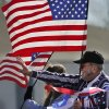 A couple wave to the crowd during the parade from the back of a pick-up tuck sponsored by Soldier Creek Baptist Church. The city of Midwest City teamed with civic leaders and local merchants to display their appreciation for veterans and active military forces by staging a hour-long Veteran\'s Day parade that stretched more than a mile and a half along three of the city\'s busiest streets Monday morning, Nov. 12, 2012. Hundreds of people lined the parade route, many of them waving small American flags that had ben distributed by volunteers who marched near the front of the parade. A fly-over performed by F-16s from the138th Fighter Wing, Oklahoma Air National Guard unit in Tulsa thrilled spectators. Five veterans representing military personnel who served in five wars and military actions served as Grand Marshals for the parade. Leading the parade was the Naval Reserve seven-story American flag, carried by 100 volunteers from First National Bank of Midwest City, Advantage Bank and the Tinker Federal Credit Union. The flag is 50 feet by 76 feet, weighs 110 pounds and was sponsored by the MWC Chapter of Disabled American Veterans. Photo by Jim Beckel, The Oklahoman