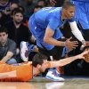 Photo - Oklahoma City Thunder guard Russell Westbrook (0) and New York Knicks guard Beno Udrih (18) scramble for a loose ball during the first half of an NBA basketball game at Madison Square Garden, Wednesday, Dec. 25, 2013, in New York. The Thunder won 123-94. (AP Photo/John Minchillo)