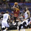 Photo - Cleveland Cavaliers' Kyrie Irving (2) makes a shot as he gets between Orlando Magic's Jameer Nelson (14) and Kyle O'Quinn, right, during the first half of an NBA basketball game in Orlando, Fla., Wednesday, April 2, 2014. (AP Photo/John Raoux)