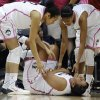Photo - Connecticut's Kaleena Mosqueda-Lewis holds her arm after a hard fall to the court as teammates Saniya Chong, left, and Moriah Jefferson, right, look over her during the first half of an NCAA college basketball game on Sunday, Feb. 9, 2014, in Storrs, Conn. (AP Photo/Jessica Hill)