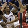 Kansas\' Wayne Selden, Jr., left, shoots as Stanford\'s Anthony Brown defends during the first half of a third-round game of the NCAA college basketball tournament Sunday, March 23, 2014, in St. Louis. (AP Photo/Jeff Roberson)