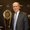 Photo - College Football Playoff Executive Director Bill Hancock poses with he College Football Playoff National Championship Trophy, Monday, July 14, 2014, in Irving, Texas. A rising gold football-shaped trophy will be the prize for the national champion in the new College Football Playoff. (AP Photo/Tony Gutierrez)