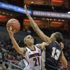 Photo - Louisville's Bria Smith, left, shoots over the defense of Central Florida's Brittini Montgomery during the first half of an NCAA college basketball game on Wednesday, Jan. 15, 2014, in Louisville, Ky. (AP Photo/Timothy D. Easley)
