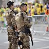 Photo - Special forces police watches Brazilian and German football fans outside the stadium prior the World Cup semifinal soccer match between Brazil and Germany at the Mineirao Stadium in Belo Horizonte, Brazil, Tuesday, July 8, 2014. (AP Photo/Martin Meissner)