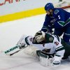 Photo - Minnesota Wild's goalie Darcy Kuemper, bottom, knocks the puck away from Vancouver Canucks' Kevin Bieksa during overtime NHL hockey action in Vancouver, British Columbia on Friday, Feb. 28, 2014. (AP Photo/The Canadian Press, Darryl Dyck)