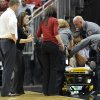 Photo - Louisville's Antonita Slaughter is placed on a stretcher by medical personnel following her collapse during the first half of an NCAA college basketball game against Missouri State, Tuesday, Dec. 3, 2013, in Louisville, Ky. (AP Photo/Timothy D. Easley)