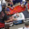An injured spectator is treated after a crash at the conclusion of the NASCAR Nationwide Series auto race Saturday, Feb. 23, 2013, at Daytona International Speedway in Daytona Beach, Fla. Driver Kyle Larson\'s car hit the safety fence sending car parts and other debris flying into the stands.(AP Photo/David Graham)