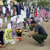 A firefighter from the Valyermo, Calif. fire department examines notes and photos left at a make-shift memorial at the Granite Mountain Hotshot Crew fire station, Friday, July 5, 2013 in Prescott, Ariz. Nearly a week after 19 Granite Mountain Hotshot firefighters died battling a blaze near Yarnell, Ariz., mourners continue to visit and grow the memorial. (AP Photo/Julie Jacobson)