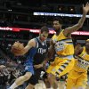 Photo - Dallas Mavericks point guard Jose Calderon (8) tiptoes along the sideline against Denver Nuggets forward Wilson Chandler (21) and Nuggets point guard Ty Lawson (3) in the second quarter of an NBA game in Denver on Wednesday, March 5, 2014.(AP Photo/Joe Mahoney)