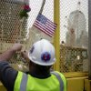 Construction worker Paddy Garvey affixes an American flag to a fence at ground zero in New York, Monday, May 2, 2011. Osama bin Laden, the face of global terrorism and architect of the Sept. 11, 2001, attacks, was killed in a firefight with elite American forces in Pakistan on Monday, May 2, 2011 then quickly buried at sea. (AP Photo/Seth Wenig) ORG XMIT: NYSW103