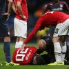 Photo - Manchester United's Robin van Persie, bottom, lies injured after colliding with Olympiakos's Kostas Manolas during their  Champions League last 16 second leg soccer match at Old Trafford Stadium, Manchester, England, Wednesday, March 19, 2014. (AP Photo/Jon Super)