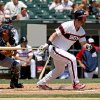 Photo - Chicago White Sox's Adam Dunn drives in the first run of a baseball game with a hit in the fourth inning as Atlanta Braves catcher Gerald Laird watches on Sunday, July 21, 2013. (AP Photo/Charles Cherney)