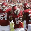 Photo - Oklahoma running back Brennan Clay (24) is congratulated by offensive lineman Gabe Ikard (64) and fullback Trey Millard (33) following his touchdown against Tulsa in the first quarter of an NCAA college football game in Norman, Okla., Saturday, Sept. 14, 2013. (AP Photo/Sue Ogrocki) ORG XMIT: OKSO109