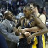 FILE - In this Nov. 19, 2004, file photo, Indiana Pacers\' Ron Artest, now know as Metta World Peace is restrained by teammate Austin Croshere and Pacers\' assistant coach Mike Brown before being escorted off the court following their fight with the Detroit Pistons and fans in Auburn Hills, Mich. NBA commissioner David Stern suspended Artest for the remainder of this season, and disciplined eight other members of the Pacers and Pistons, sending a strong message that the league won\'t tolerate the type of unprecedented violence displayed that night. The brawl was speculated to stand among the worst in league history. (AP Photo/Duane Burleson, File) ORG XMIT: NY153