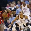 Miami Heat forward LeBron James, left, keeps the ball from Oklahoma City Thunder guard Russell Westbrook (0) in the fourth quarter of an NBA basketball game in Oklahoma City, Thursday, Feb. 14, 2013. Thunder forward Kevin Durant (35) watches at rear. Miami won 110-100. (AP Photo/Sue Ogrocki) ORG XMIT: OKSO114