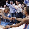 Thunder fans react as Oklahoma City\'s Eric Maynor (6) helps Daequan Cook (14) get up after Cook made a three-point baskte in the second half of an NBA basketball game between the Oklahoma City Thunder and the Dallas Mavericks at Chesapeake Energy Arena in Oklahoma City, Thursday, Dec. 29, 2011. Oklahoma City won, 104-102. Photo by Nate Billings, The Oklahoman