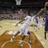 Texas\' Cameron Ridley (55) and Kansas\' Elijah Johnson (15) leap for a rebound during the first half of an NCAA college basketball game, Saturday, Jan. 19, 2013, in Austin, Texas. (AP Photo/Eric Gay)