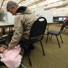 Tim Grotto plays with his 3-month-old daughter Mary as he votes at the Peosta Community Center in Peosta, Iowa on Tuesday Nov. 6, 2012. (AP Photo/The Telegraph Herald, Dave Kettering)