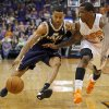 Photo - Utah Jazz guard Trey Burke (3) drives past Phoenix Suns guard Eric Bledsoe during the second half of an NBA basketball game on Saturday, Nov. 30, 2013, in Phoenix. (AP Photo/Matt York)