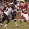 Oklahoma\'s Landry Jones (12) tries to get away from Texas Tech\'s Cqulin Hubert (51) and Sawyer Vest (34) during the college football game between the University of Oklahoma Sooners (OU) and Texas Tech University Red Raiders (TTU) at the Gaylord Family-Oklahoma Memorial Stadium on Sunday, Oct. 23, 2011. in Norman, Okla. Photo by Chris Landsberger, The Oklahoman