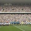 Photo - Corinthians's and  Figueirense players listen the national anthem prior to a Brazilian soccer league match at the Itaquerao, the still unfinished stadium that will host the World Cup opener match between Brazil and Croatia on June 12, in Sao Paulo, Brazil, Sunday, May 18, 2014. Only 40,000 tickets were put on sale for Corinthians' match against Figueirense because some of the 20,000 temporary seats needed for the World Cup opener are still being installed. (AP Photo/Andre Penner)