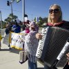 Jackie Maye, plays her accordion during a protest against Wal-Mart in Boynton Beach, Fla., Friday, Nov 23, 2012. Wal-Mart employees and union supporters are taking part in today\'s nationwide demonstration for better pay and benefits A union-backed group called OUR Walmart, which includes former and current workers, was staging the demonstrations and walkouts at hundreds of stores on Black Friday, the day when retailers traditionally turn a profit for the year. (AP Photo/J Pat Carter)