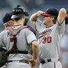 Photo - Minnesota Twins starting pitcher Kevin Correia (30) adjusts his cap as he talks with catcher Joe Mauer (7) and  pitching coach Rick Anderson (40) in the first inning of a baseball game against the Atlanta Braves Monday, May 20, 2013, in Atlanta. (AP Photo/John Bazemore)