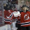 Photo - New Jersey Devils' Marek Zidlicky, front right, of the Czech Republic, celebrates his goal with the bench during the first period of an NHL hockey game against the Boston Bruins in Newark, N.J., Sunday, April 13, 2014. (AP Photo/Mel Evans)